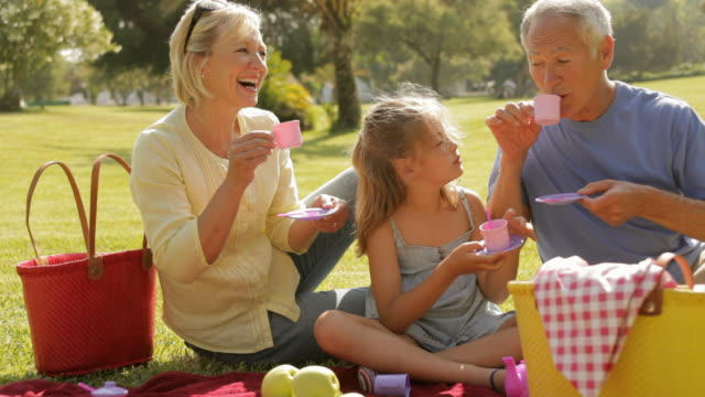 grandparents and granddaughter playing with teaset in park