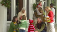 MS Grandparents greeting family with Christmas presents at front door of home / Richmond, Virginia