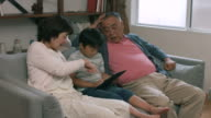 Grandparents sat with their grandson using a digital tablet