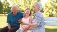 Grandparents using tablet with granddaughter while sitting in the park