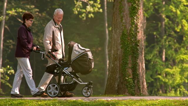 SLO MO nonni piedi con i loro nipoti maschi e femmine nel passeggino
