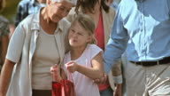SLO MO grandparents with granddaughter walking and talking after shopping