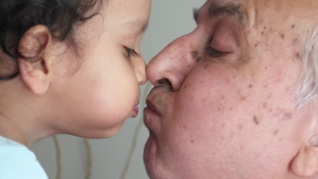 Grandson and his Grandfather sharing intimate moments of love and togetherness, kissing, talking and hugging.