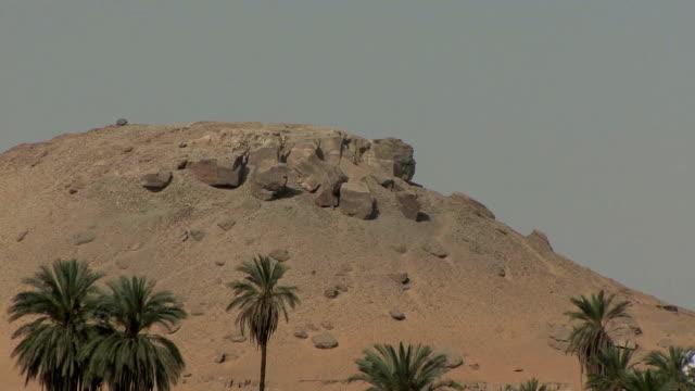 POV ZO Granite rocks on mountaintop and view of Nubian village by Nile, Aswan, Egypt