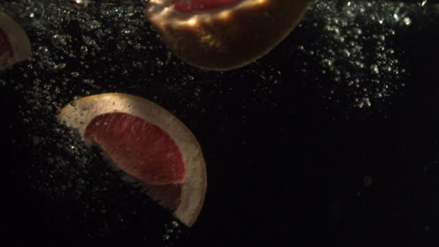 Grapefruit segments falling into water, black background
