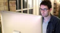 Graphic designer gazes at computer screen
