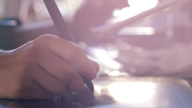 Graphic Designer Using Digital Tablet and Pen