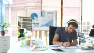 Grafisch ontwerper arbeids- en luisteren naar muziek