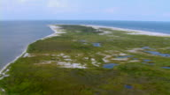 Grassy marshes surround small coastal pools on Cat Island in Mississippi.