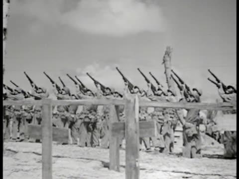 Gravesite w/ Christian crosses marking graves WS Marines firing 21 gun salute Marine playing 'Taps' on bugle US Marines w/ heads bowed World War II...