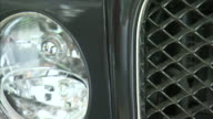 A gray Bentley features an ornate grill.