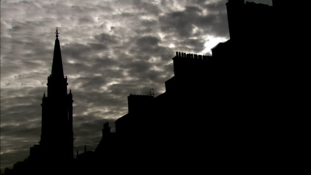 Gray clouds hover in the sky over a silhouetted church steeple and city wall. Available in HD.