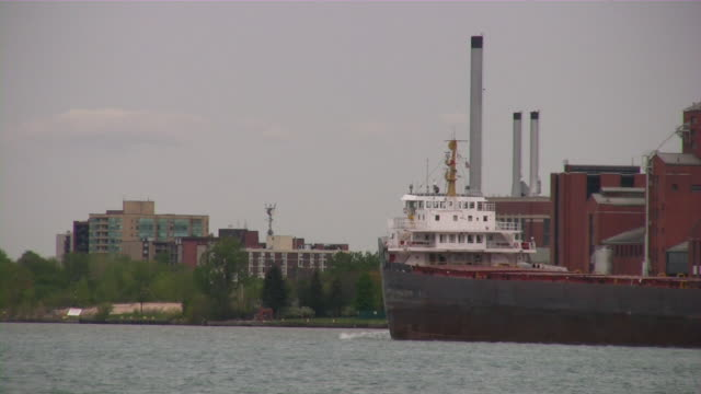 Great Lakes Freighter on Detroit River (Michigan). Windsor, Canada background.