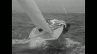MS great shot of Starclass yacht racing toward camera as its two man crew hang onto the side prevent capsizing another boat in background / MS boat...