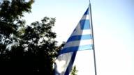 Greek flag flying in sunset