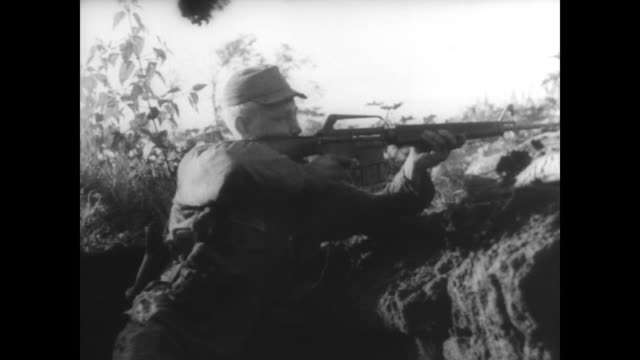Green Beret soldiers fighting in Vietnam during Operation Hawthorne / soldiers behind sand bags / firing at Viet Cong from trench / African American...