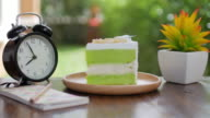 Green Cake Matcha green tea cream cake on wooden table for relax time , dolly shot tilt up