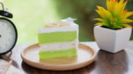 Green Cake Matcha green tea cream cake on wooden table for relax time , dolly shot right to left