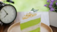 Green Cake Matcha green tea cream cake on wooden table for relax time , dolly shot