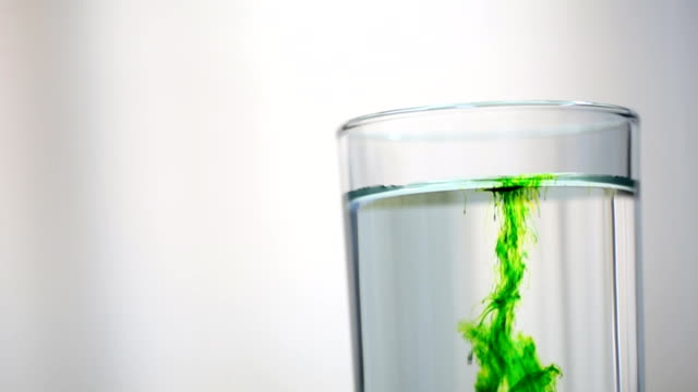 Green dye  drop in to water glass