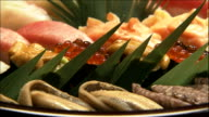 Green garnishes complement a tray of nigiri-sushi.