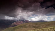 Green hills lead to rugged mountains in the Humahuaca Valley of Argentina. Available in HD.