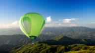 Green Hot air balloon fly over mountain