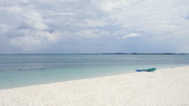 WS Green kayak on white sandy beach / Nikkoi Island, Bintan, Indonesia