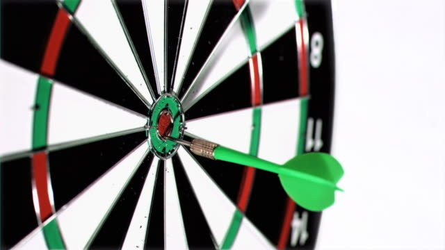 Green plastic dart in a super slow motion thrown at the middle of a dart board