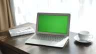 Green screen Laptop display with a cup of coffee on the wood desk, Dolly shot