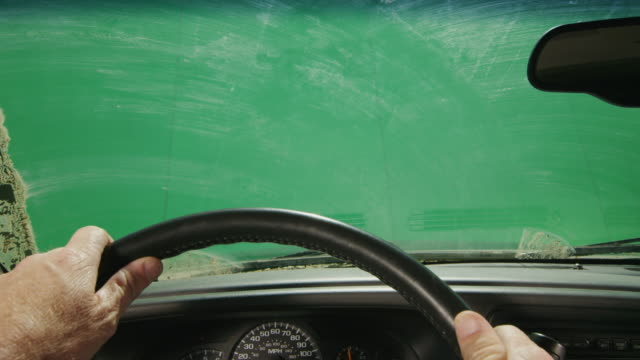 Green screen POV through the dirty windshield of a truck as a man drives.