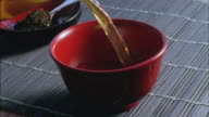 CU, Green tea being poured into traditional Japanese cup