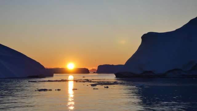 Greenland by boat, sun slides over the iceberg