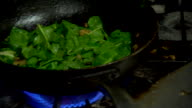 Greens apples cooking in skillet hands stirring food putting it into bowl taking it away Vegan vegetarian health food
