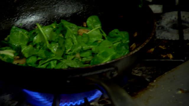 Greens apples cooking in skillet hands stirring food putting it into bowl taking it away Vegan vegetarian health food