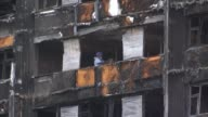 Death toll may be lowered as police investigate cases of fraud ENGLAND London North Kensington EXT Trees with burned out shell of Grenfell Tower...