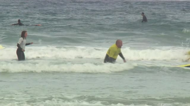 Firefighters who saved lives go surfing in Cornwall ENGLAND Cornwall Penzance EXT Various of London firefighters on beach and surfing Oliver Hibberd...