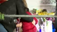 Pensioner Luna Nordi tends shrine North Kensington EXT Girl and woman looking at shrine for victims of Grenfell Tower fire Luna Norde in shot Woman...