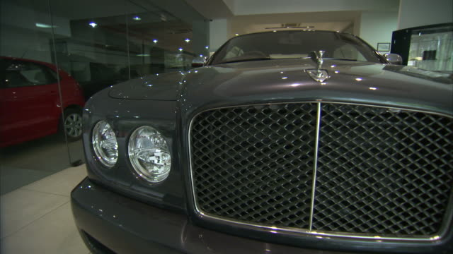 A grey Bentley sits in a dealership showroom.