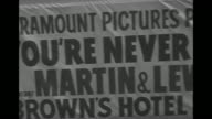 Greyhound charter bus approaches bearing sign touting preview of movie 'You're Never Too Young' at Brown's Hotel / comedian Jerry Lewis in bellhop...