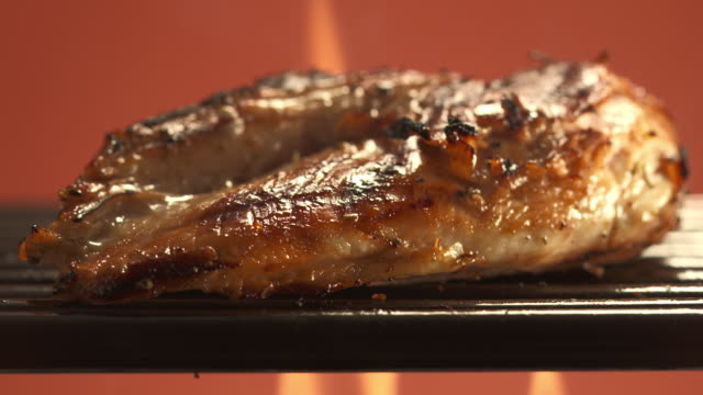 CU Grilled chicken breast being flipped over on open grill / Los Angeles, California, United States