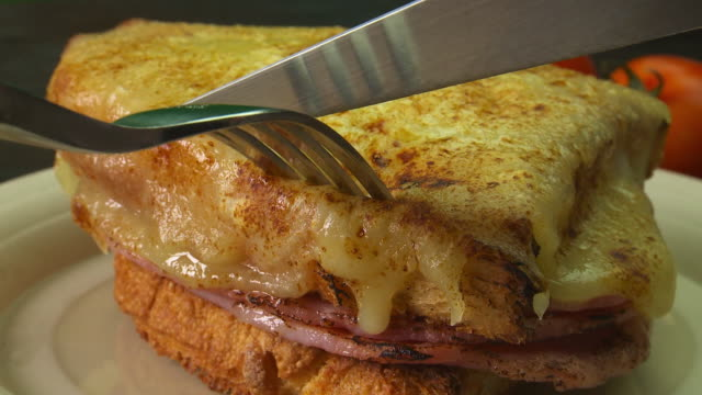 grilled ham and cheese sandwich being eaten.