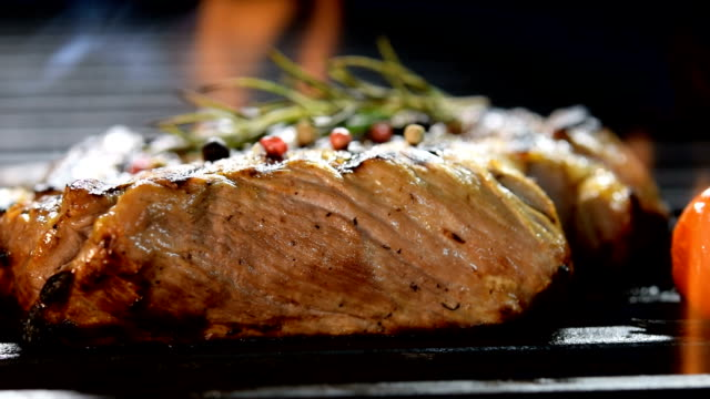Grilled meat /steak with vegetable on the flaming grill - slow motion