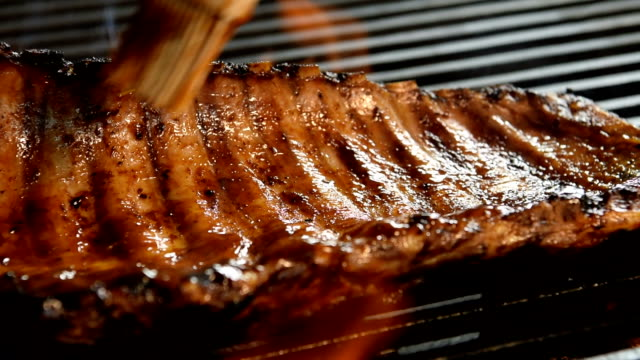 Grilled pork ribs with Barbecue sauce on the flaming grill - slow motion