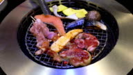 Grilling meats and seafood in japanese style on hot charcoal grill