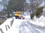 Gritter lorry with snow plow passes by on snowy road Scotland