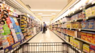 Grocery cart POV rolls down a food aisle past other shoppers.