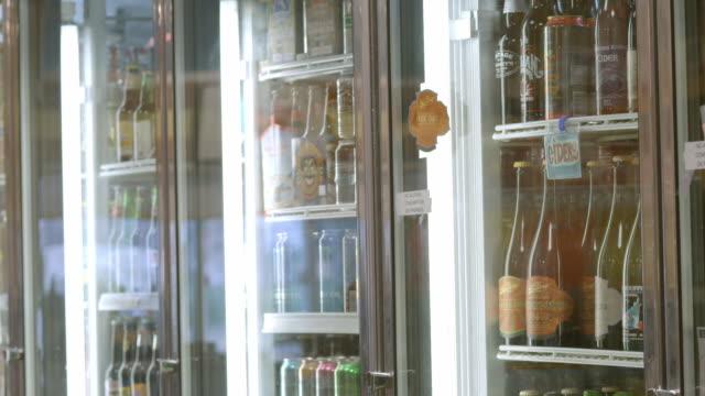 grocery store customer walks up to beverage display cooler opens door and retrieves two bottles of beer / Redlands, California, USA