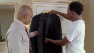 Groom getting dressed showing best man tuxedo on morning of wedding day