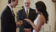 MS ZI Groom putting wedding ring on bride's finger in front of minister / Las Vegas,Nevada,USA